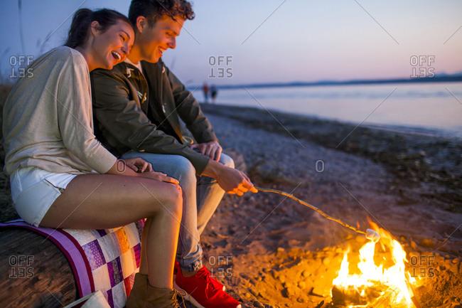 Couple roasting marshmallows on fire at beach