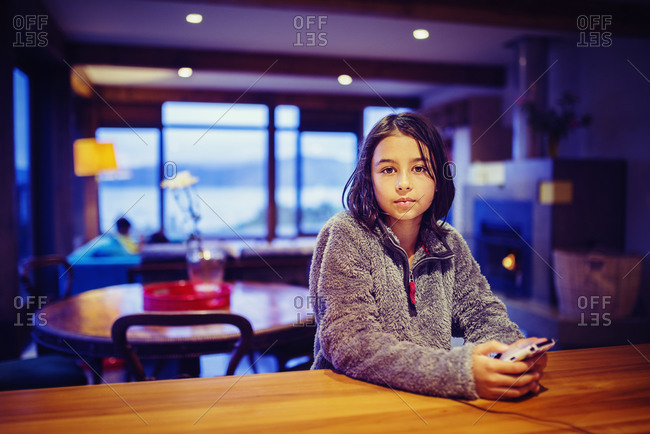 Girl using cell phone at table
