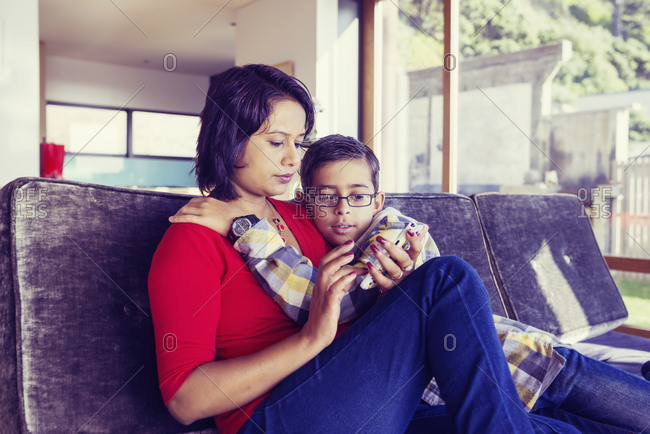 Mother and son using cell phone in living room