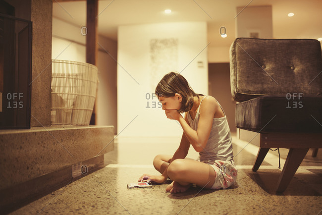 Girl using cell phone in living room