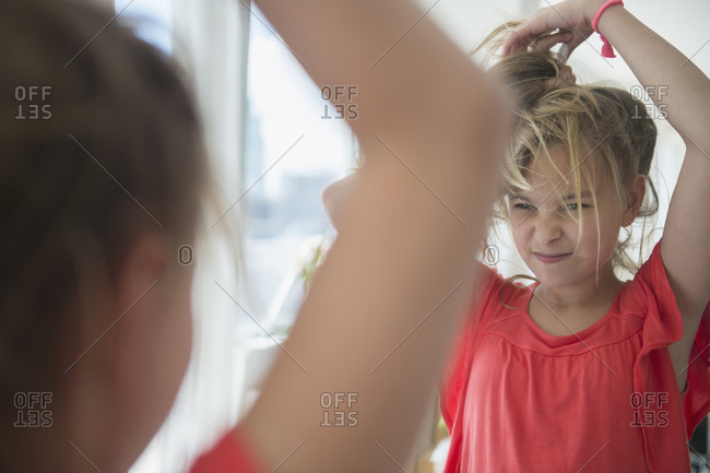 Girl playing with her hair at mirror