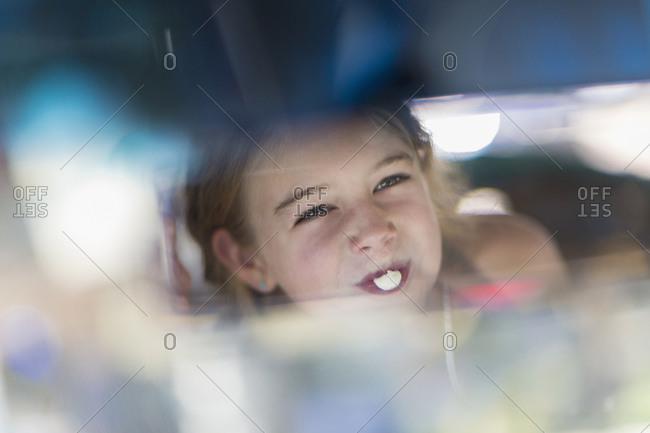 Reflection of Girl blowing bubble gum bubble in rearview mirror