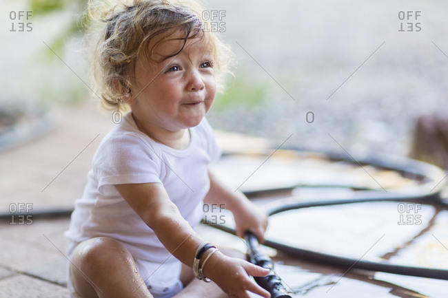 Toddler boy playing with hose