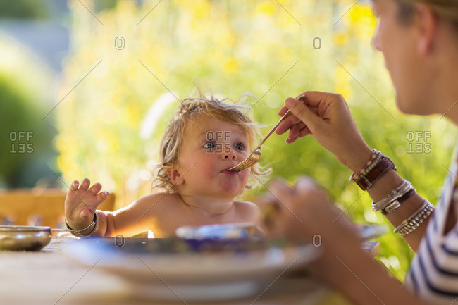 Mother feeding baby son at table