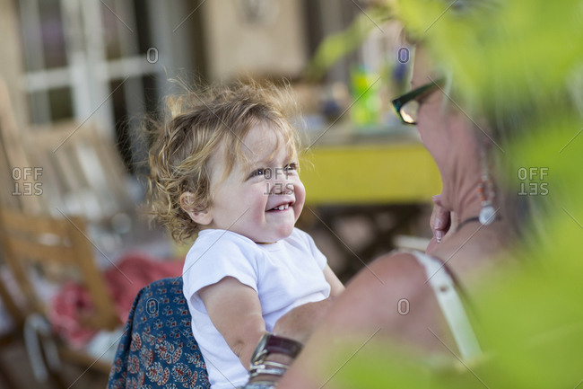 Grandmother and baby grandson smiling outdoors