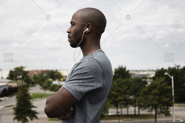 Runner listening to ear buds in urban park