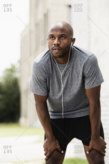 Runner resting in city with ear buds