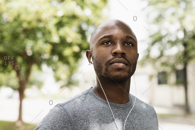 Runner resting in park with ear buds