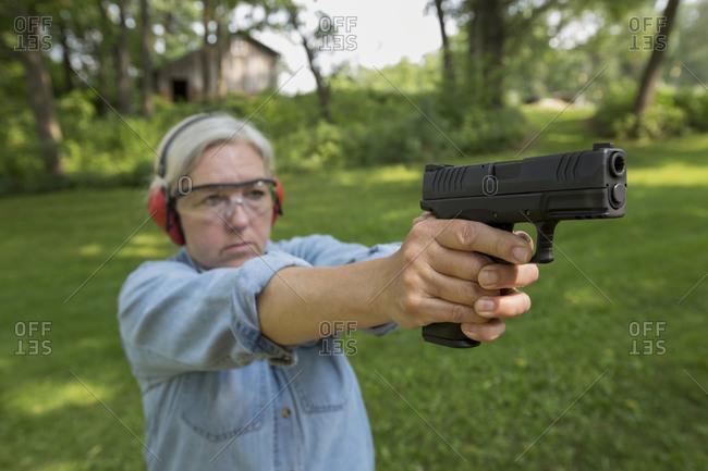 Older Woman practicing with gun at shooting range
