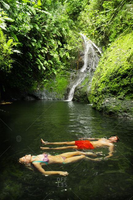 Couple floating in remote jungle pool