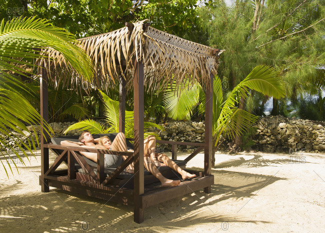 Couple relaxing in cabana on tropical beach