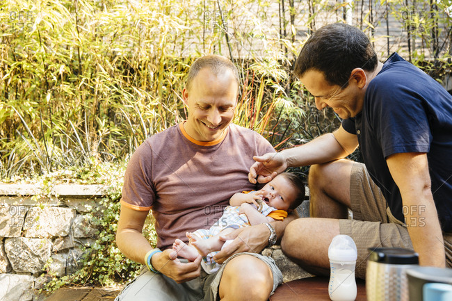 Gay couple admiring baby boy in backyard