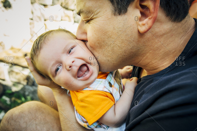 Father kissing baby boy outdoors