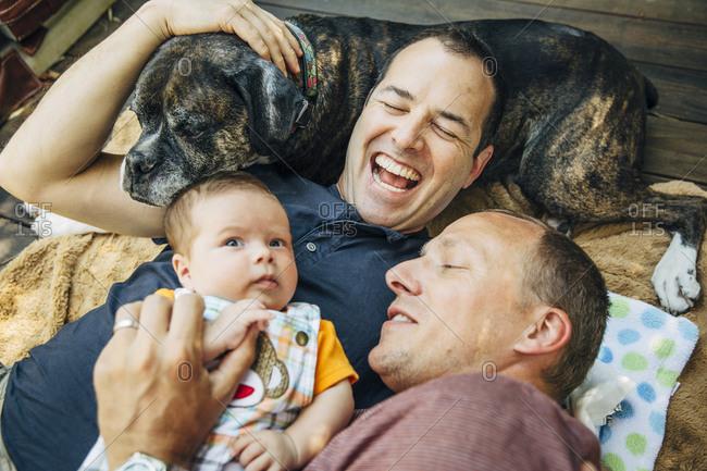 Gay couple cuddling baby boy and dog