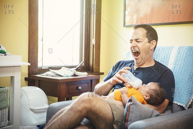 Yawning Father feeding baby boy in living room