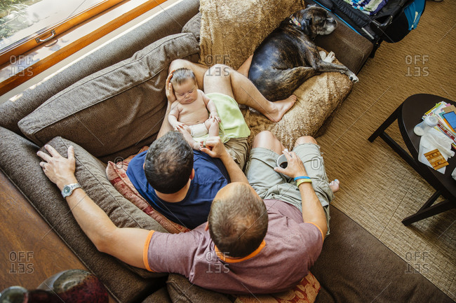 Gay couple holding sleeping baby boy on sofa