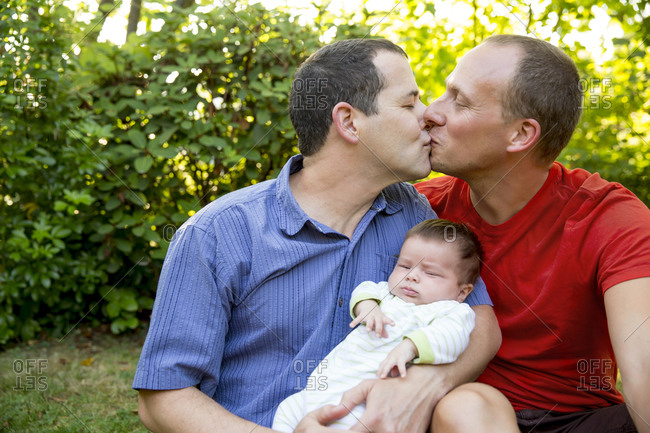 Gay couple kissing with baby boy in backyard