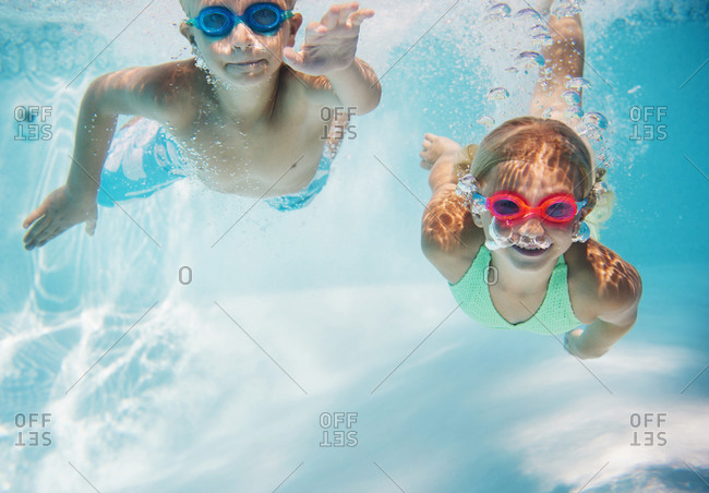 Children swimming underwater in pool