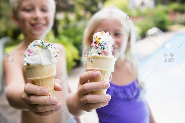 Children eating ice cream near swimming pool