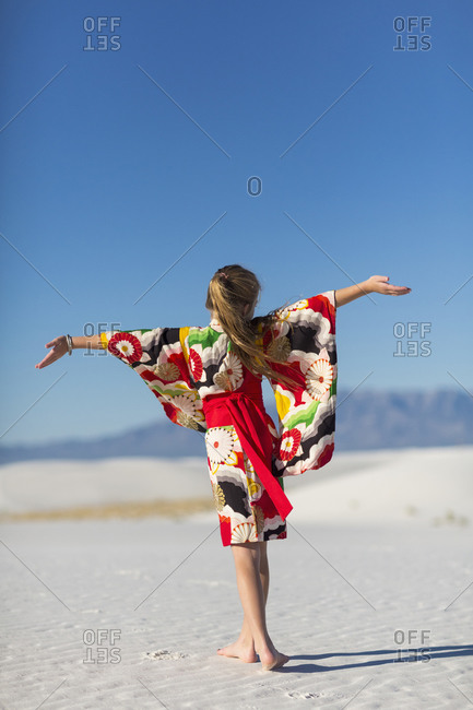 Girl with arms outstretched on sand dune