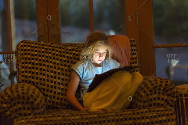 Girl using digital tablet in armchair at night