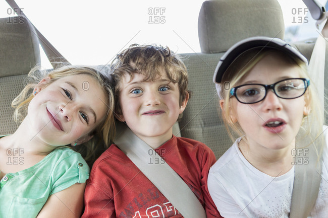 Children smiling in back seat of car