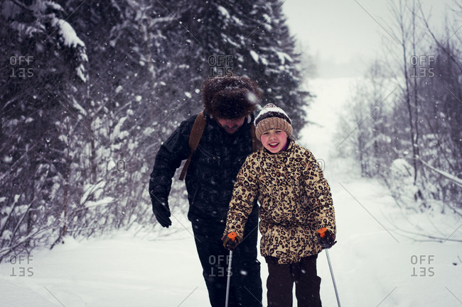 Father and daughter cross-country skiing on snowy road
