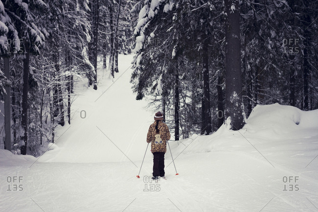 Girl cross-country skiing in forest