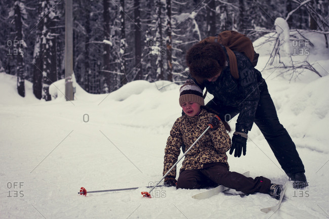 Father helping cross-country skiing daughter falling in snow