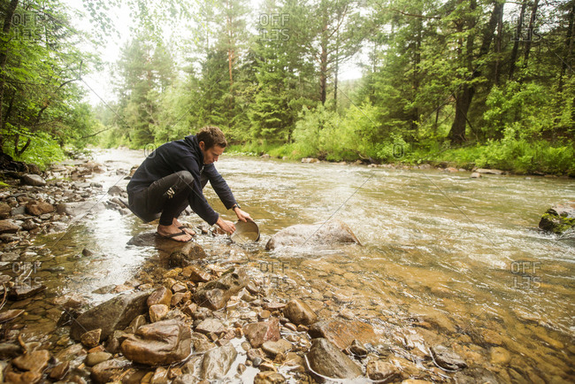 Man crouching in forest river