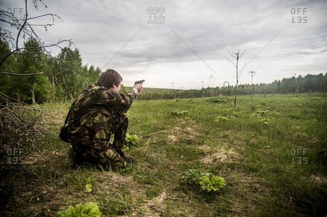 Man practicing shooting in rural field