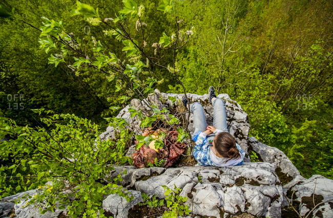 High angle view of Girl sitting on cliff edge