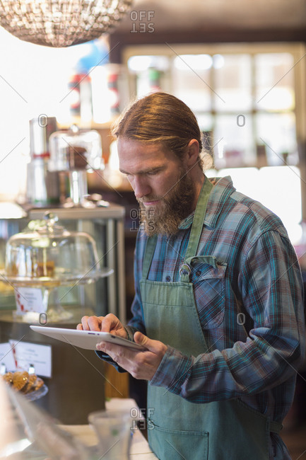 Server using digital tablet in cafe