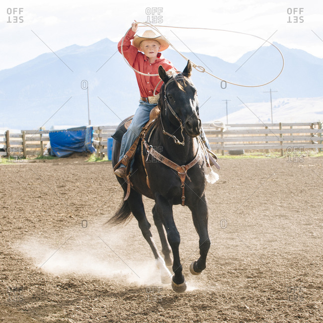 Boy using lasso on horse at rodeo