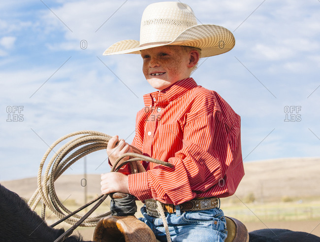 Boy on horse carrying lasso