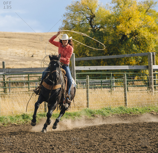 Woman using lasso on horse at rodeo