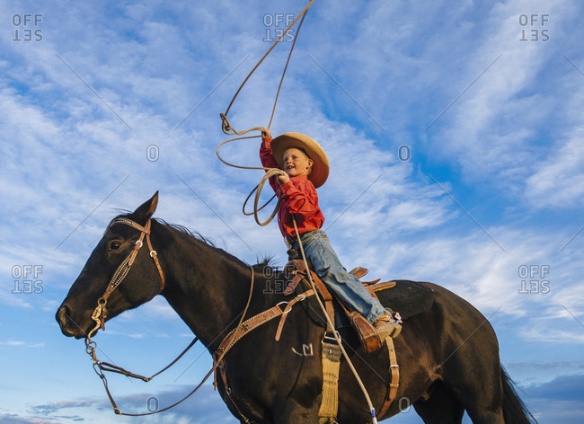 Low angle view of Boy on horse throwing lasso