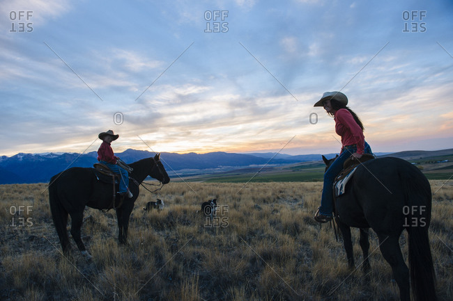 Mother and son riding horses in remote field