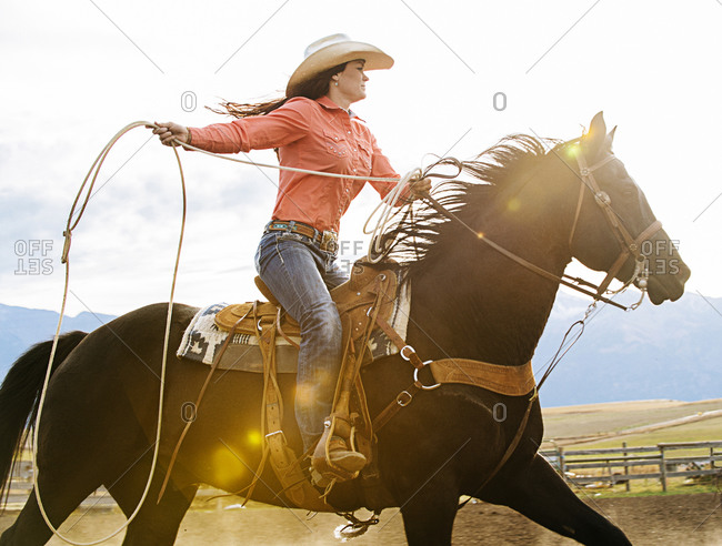Woman on horse throwing lasso at rodeo
