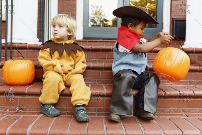 Boys in costumes trick sitting on front stoop on Halloween