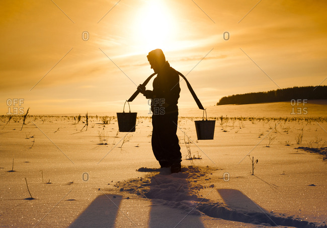 Silhouette of Man carrying buckets on traditional yoke in snowy field