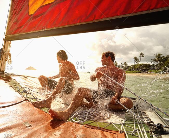 Men steering sailboat in ocean