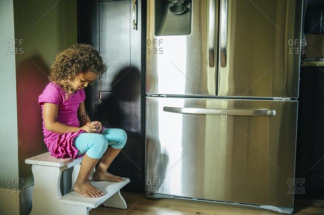 Sad mixed race girl sitting near refrigerator