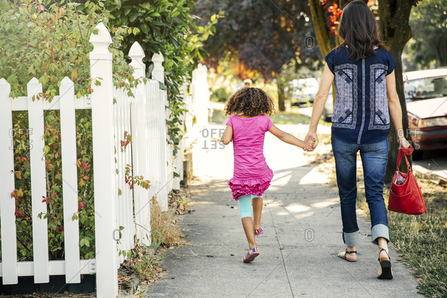 Mother and daughter holding hands on sidewalk