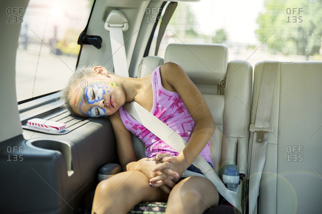 Girl in face paint sleeping in car back seat