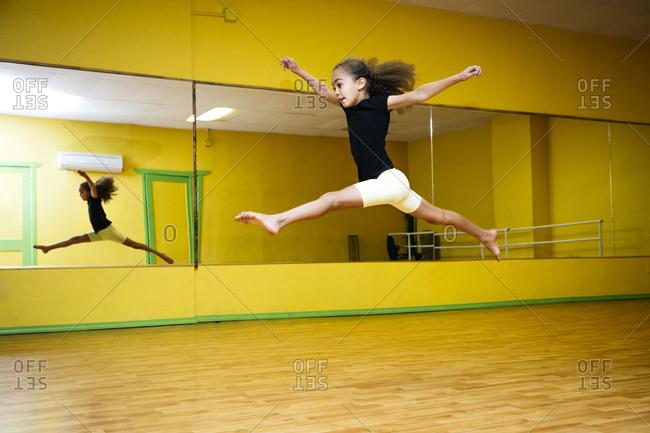 Girl leaping in ballet studio
