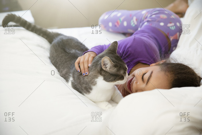Girl playing with cat on bed