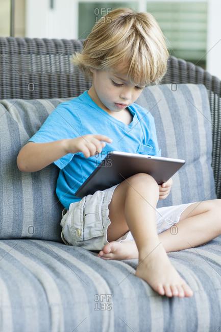 Boy using digital tablet on sofa