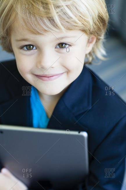 Smiling Boy in business suit holding digital tablet