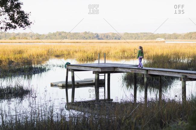 Girl walking on wooden dock in lake